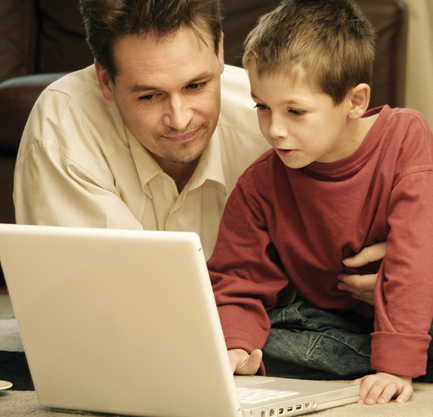 A father and son at home using a white laptop