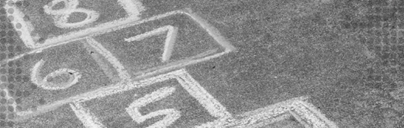 Photo of pavement with markers for a game of hopscotch drawn onto it