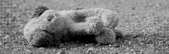 Photo of a teddy bear lying on pavement