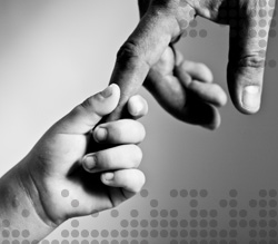Photo of a child's hand holding an adult's hand
