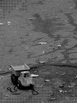 Photo of a toy truck on cracked pavement