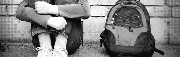 Photo of a child sitting outside with their knapsack, holding their arms tightly around their legs